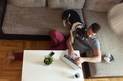 man using laptop and home with dog